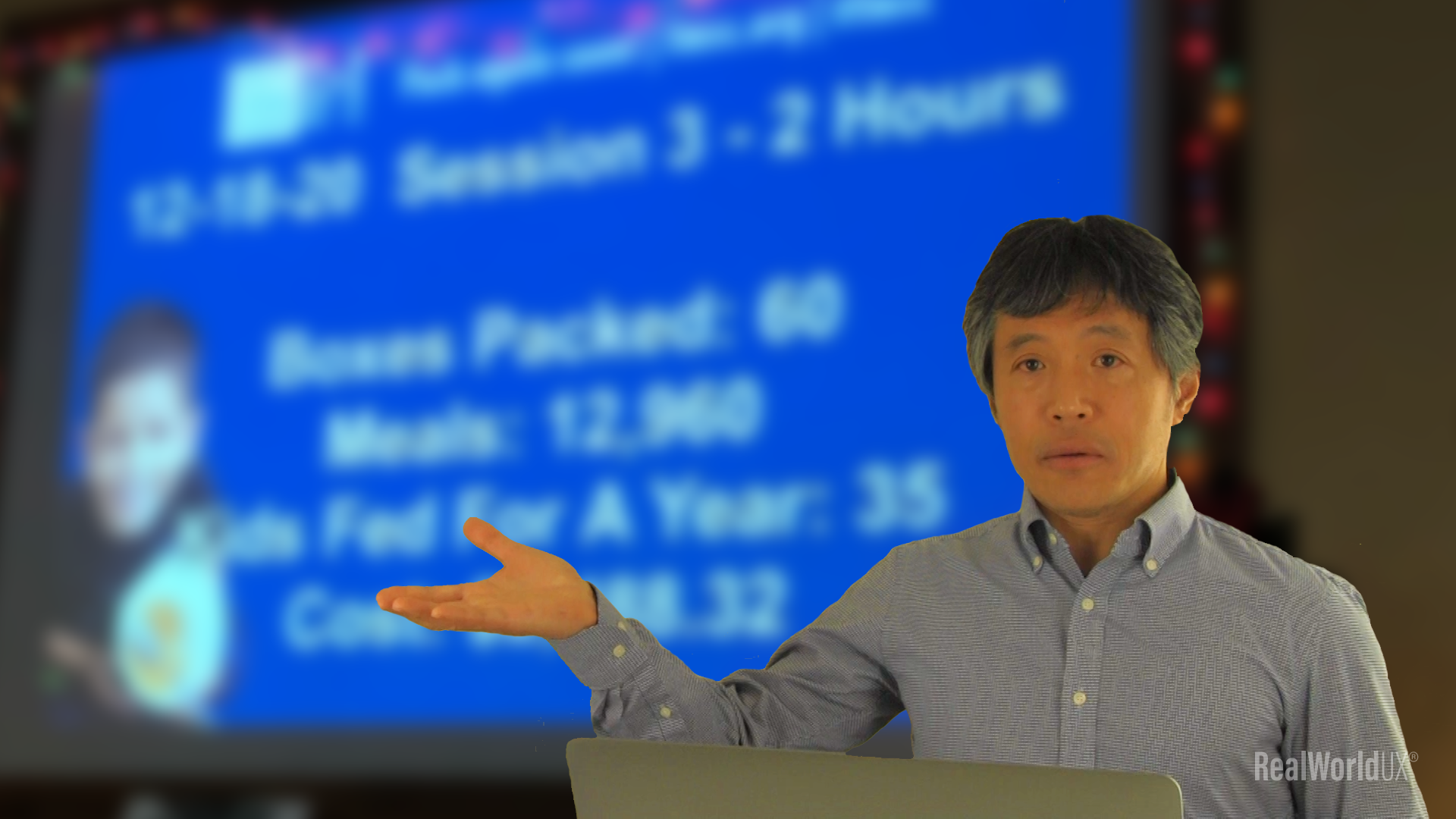 Author in front of a blurred image of a volunteer session result presentation screen