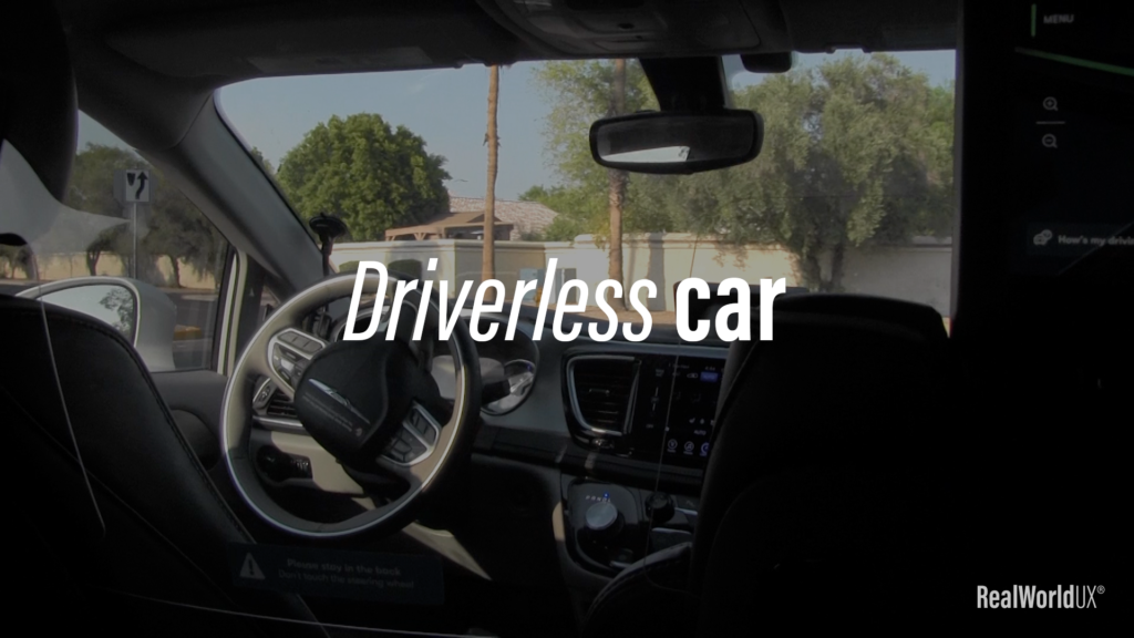 """A photo of inside Waymo with an empty driver seat, with a text """"Driverless car"""" on top."""